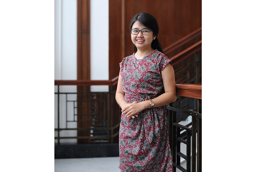 A woman with glasses and batik dress is standing in front of staircase