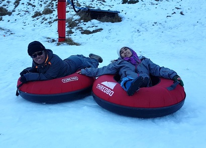 A man and woman with winter clothing are on the snow tire