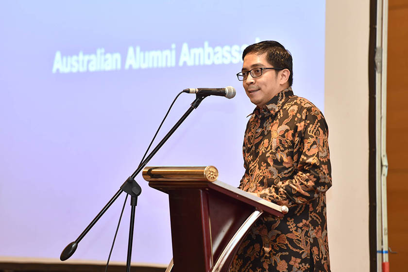 A man with glasses wearing formal batik shirt giving speech on the podium