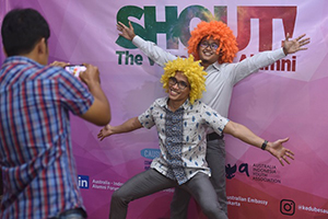 Two men are taken a photo wearing clown wigs