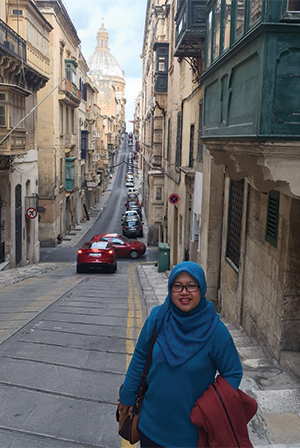 A woman with blue hijab wearing blue long sleeve tshirt standing on the pedestrian
