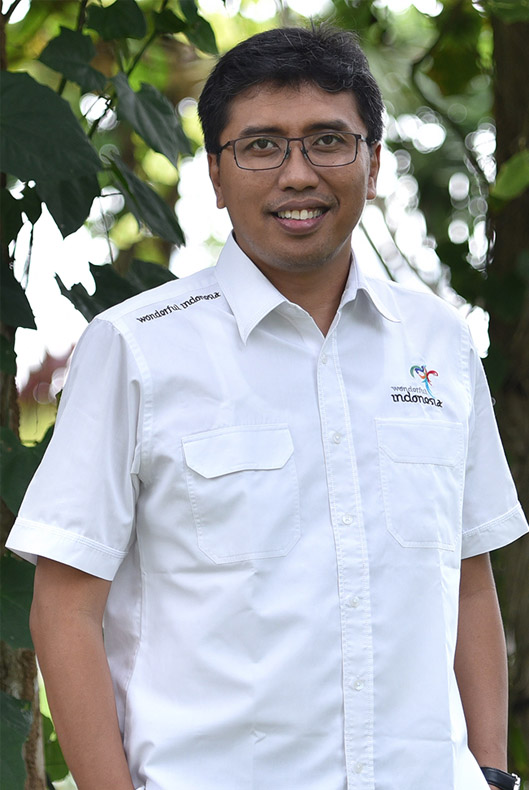 A man with glasses wearing a white shirt with wonderful Indonesia logo on the chest