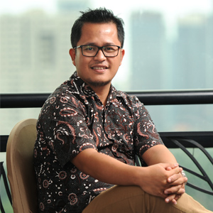 A man with glasses wearing black batik shirt sitting on the sofa
