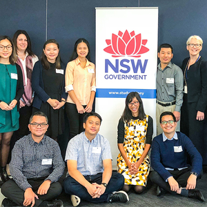 A group of people smiling with the NSW government banner at the back
