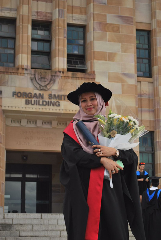 A woman with hijab with graduation attire holding a flower bouquet