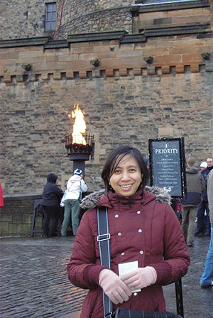 A woman wearing red jacket is standing in front of a castle