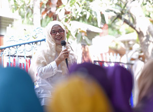 A woman with hijab and red glasses is talking holding a microphone to a group of women