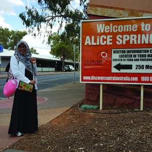 A female student standing in front of Alice Springs signboard