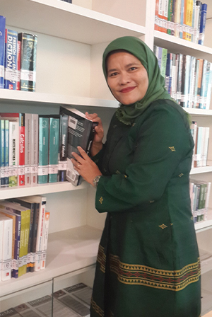 A woman with green hijab w earing green dress is taking a book from the book shelf